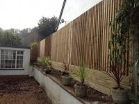 Close board with extra thick gravel boards to retain soil on the other side of fence<br>